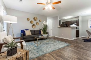 Spacious living room with ample seating, ceiling fan, and view of kitchen at The Willows apartments for rent in Spartanburg, SC
