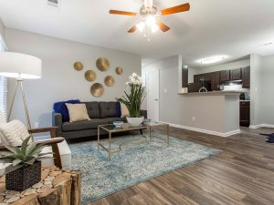 Spacious living room with ample seating, ceiling fan, and view of kitchen at The Willows apartments for rent