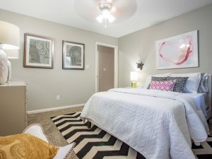 Furnished bedroom with ceiling fan at The Willows apartments for rent