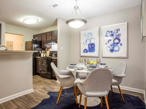 Dining area with four chairs and table and view of kitchen at The Willows apartments for rent