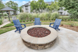 Outdoor seating area with three blue chairs at The Willows apartments for rent