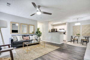Open-concept living room with ample seating, ceiling fan, and views of dining room and kitchen at The Willows apartments for rent