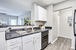 Kitchen with dishwasher, sink, and white cabinetry at The Willows apartments for rent