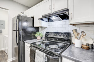 Kitchen with black appliances and white cabinetry at The Willows apartments for rent in Spartanburg, SC