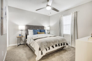 Furnished bedroom with ceiling fan and window for natural light at The Willows apartments for rent