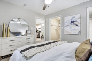 Furnished bedroom with ceiling fan, walk-in closet, and views of dining area and kitchen at The Willows apartments for rent