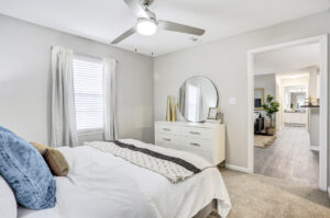 Furnished bedroom with ceiling fan and view of living room at The Willows apartments for rent